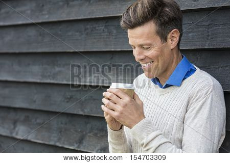 Portrait shot of an attractive, successful and happy middle aged man male outside drinking coffee in a disposable takeaway cup.