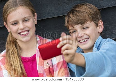Two children boy and girl talking cell phone selfie photograph
