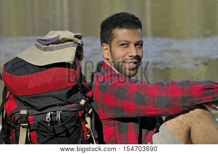 Portrait of happy backpacker sitting outdoor with backpack