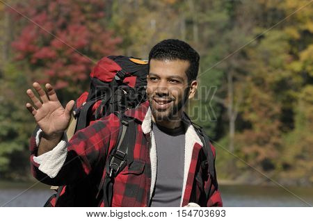 An outdoor portrait of happy young latin man with casual clothing and backpack