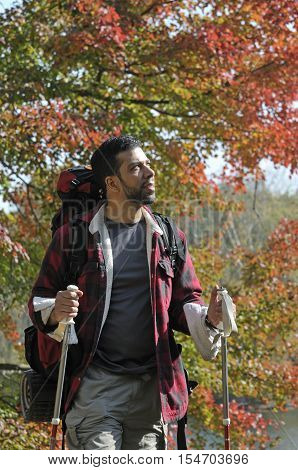 Hispanic Man Trekking in the outdoors with backpacking gear with fall trees in background