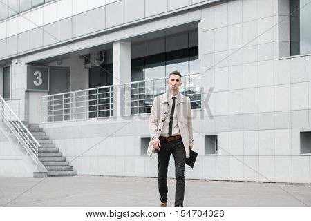 Succesful businessman walking down the street and smiling in daylight. Half length of young handsome black hair caucasian modern businessman. Business working concept