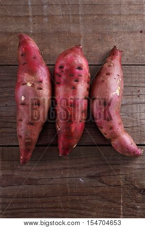 Three Red Sweet Potatoes Over Rustic Wooden Background
