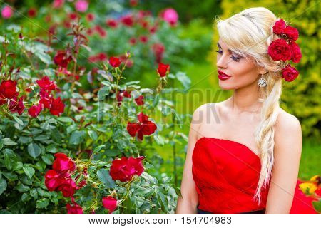 half length portrait of beautiful woman in red dress in summer park sitting on grass and looking at flowers