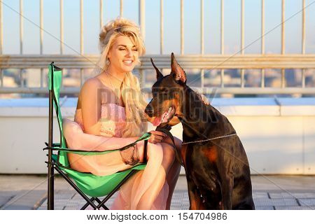 Happy beautiful blonde in a pink dress sitting on a folding chair near the Doberman on the roof