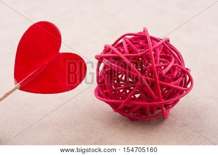 Little red color heart shape at the top of a stick and a red straw spool