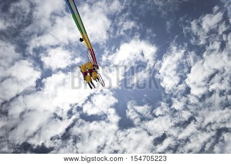 Teens on a ride at a fairground blue sky on background