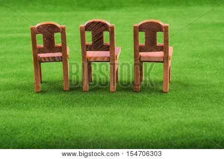 Brown color wooden toy chair on artificial grass