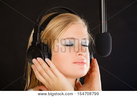 Music passion stage-fright concept. Blonde young woman singing to microphone and wearing big headphones on her head performing songs in studio.