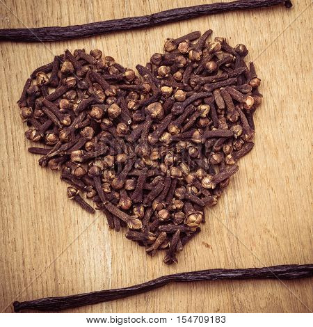 Heart form made from spice cloves on wooden background
