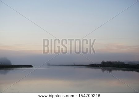 Fog over calm river on cold October morning