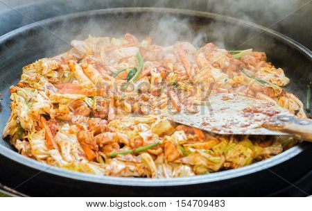 One of Korean favorite : Korean spicy stir fried vegetable, chicken and Korean spicy sauce (Gochujang) in big hot pan know as Dak Galbi