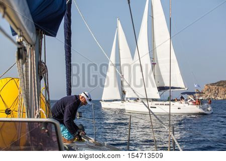 Man skipper on the sailing boat during yacht regatta on the Sea.