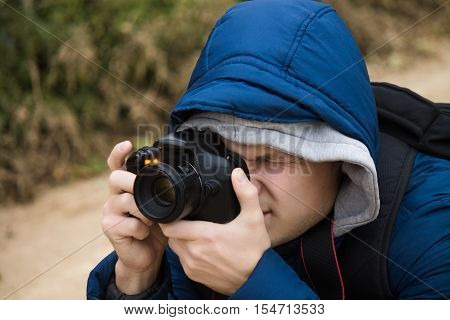 Young photographer is taking photo on DSLR camera. He narrowed his eyes and looking at the viewfinder