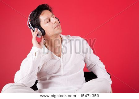 young men listening to music at his home next to a red wall