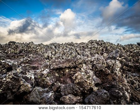 Black lava rock and cloudy, dramatic sky