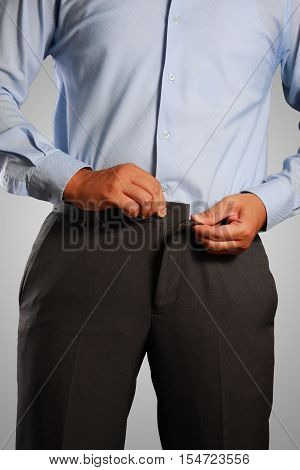 Photo image of a businessman dressing pulling his pants placket. Closeup shot of male waist dressing wearing a pants. Formal wear