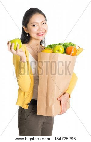 Happy young Asian female shopper, hands holding shopping bags filled with groceries and smiling, isolated standing on white background.