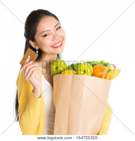Happy young Asian female shopper, hands holding shopping bags filled with groceries and showing credit card, isolated standing on white background.