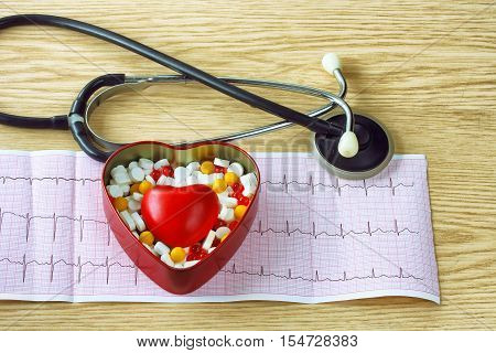 cardiogram stethoscope with tablets box and red heart on wooden table