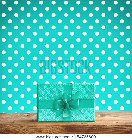 holiday turquoise gift box with a bow on wooden table background with polka dots retro vintage style