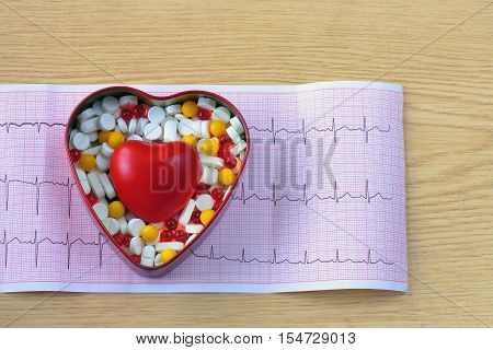 cardiogram box of pills and heart on wooden table