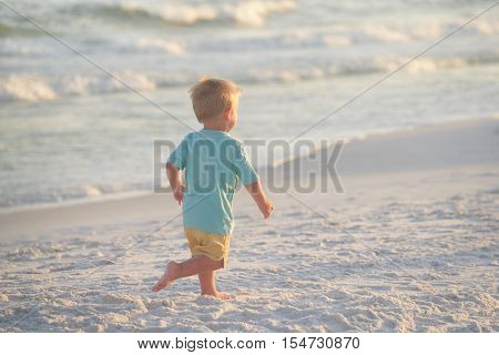 Little boy in blue shirt and yellow shorts running on sand on the beach towards setting sun near ocean waves.