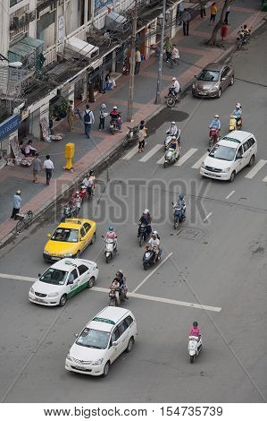 Ho Chi Minh Vietnam-October 25 2009. View from above down onto a street scene with scooters pedestrians and taxi cabs in Ho Chi Minh City (Saigon) Vietnam