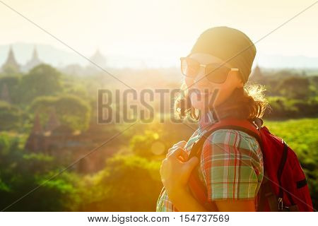Portrait a smiling young woman traveler with a backpack on the background of the sunset over the ancient temples. Traveling freedom and active lifestyle concept.