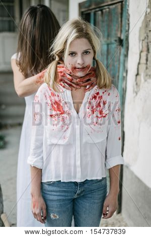 Brunette ghost woman strangle blood covered blonde woman