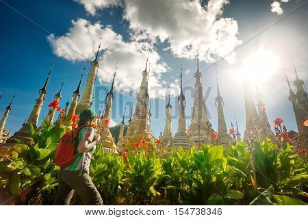 Woman traveling with backpack looking at stupa Buddhist temple Takhaung Mwetaw Pagoda . Myanmar