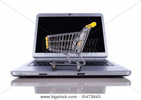 shopping-cart over a laptop isolated on white with reflection