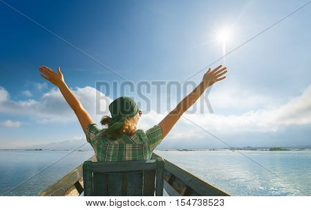 Happy carefree woman in travels by boat . Traveller woman in sunshine glow of sun with arms outspread and face raised in sky enjoying open spaces on lake serenity in nature.