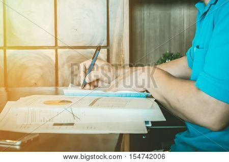 Business Man working at office hand holding pen point stock maket document and smartphone on his desk.