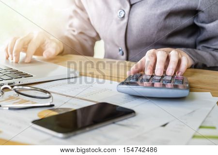 Business woman hand pointing calculator and using laptop computer for calculate stock maket chart of This month.