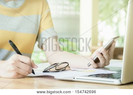 close up spectacles with business woman hand holding smartphone with pen point stock maket document and use laptop.