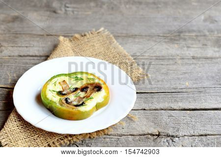 Scrambled eggs with mushrooms in green pepper. Scrambled eggs on a plate isolated on old wooden background with blank copy space for text