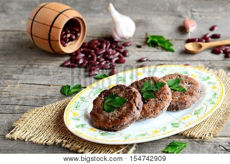 Delicious bean burgers with garlic and spices on a plate. Small decorative barrel with raw red beans, garlic, parsley on an old wooden background. Vegetarian burgers. Rustic style