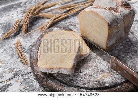Baking and cooking concept background. Cut white toast bread loaf with knife on rustic wood sprinkled with flour. Stained dirty surface of table.