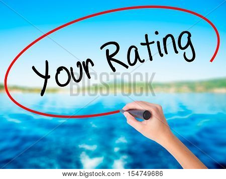 Woman Hand Writing Your Rating With A Marker Over Transparent Board.
