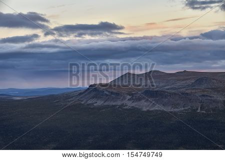 Sarek sunset over vibrant colored mountain ridge grown by pine forest