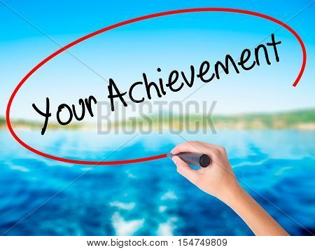 Woman Hand Writing Your Achievement With A Marker Over Transparent Board.