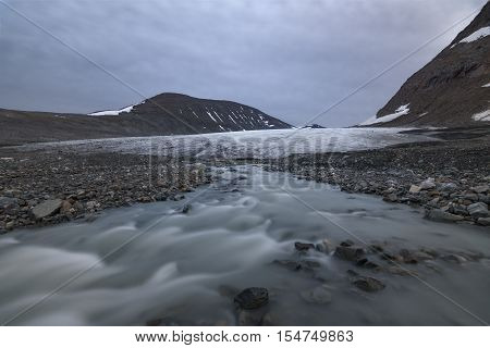 Serene glacier with river arising underneath, Sarek national park, Sweden