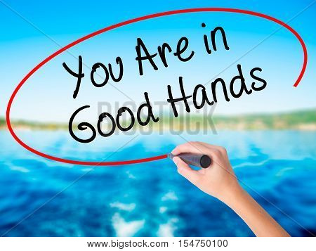 Woman Hand Writing You Are In Good Hands With A Marker Over Transparent Board