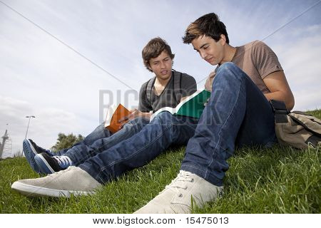two young student reading books at the school park