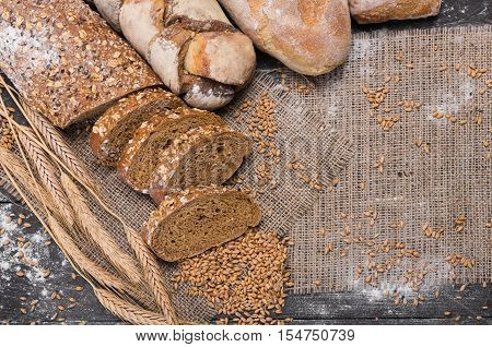 Plenty of sliced rye bread background. Bakery and grocery concept. Fresh, healthy whole grain sliced sorts of rye and white loaves, sprinkled flour on sackcloth with copy space