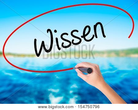 Woman Hand Writing Wissen (know In German)  With A Marker Over Transparent Board