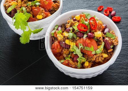 Chili con carne in a white ceramic bowl on black stone background. Cooked with ground beef tomatoes peppers beans corn garlic onion cilantro.