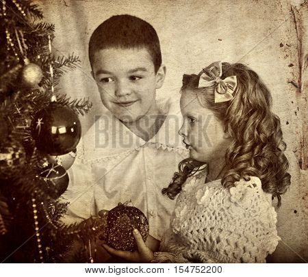 Retro portrait of children brother and sister decoration Christmas tree. Black and white retro picture on yellow paper.