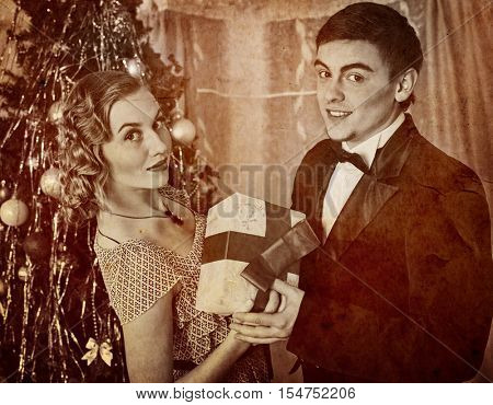 Retro vintage portrait of couple on party near Christmas tree. Black and white retro on old paper.